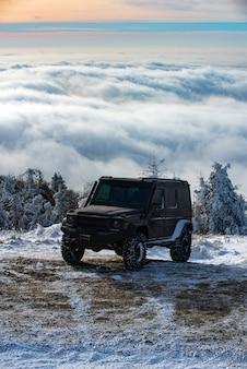 Concept de ravel d'hiver avec voiture 4x4. voiture d'hiver tout-terrain. voyage d'aventure. voyage hors route sur la route de la montagne enneigée.