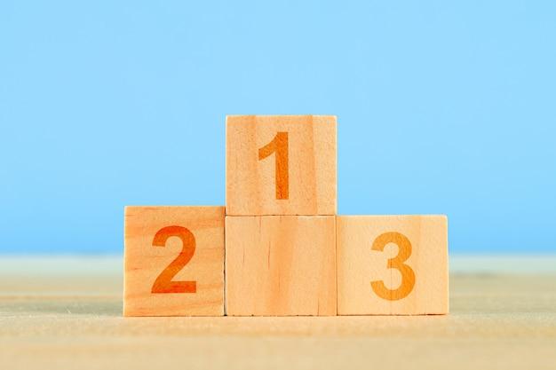 Concept de réalisation. podium en bois debout sur fond bleu.