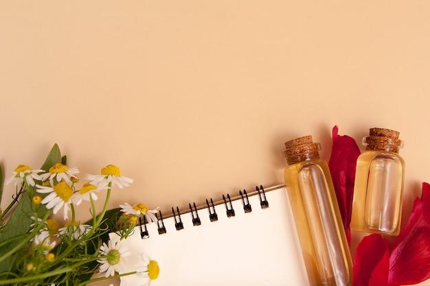 Concept de recettes de beauté. cahier, bouteilles d'essence, pétales, marguerites à plat avec espace copie