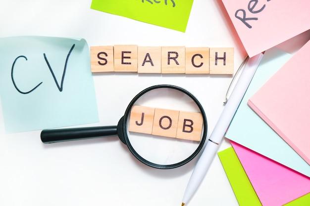 Concept de recherche d'emploi. lettrage de recherche d'emploi sur la table, nombreuses feuilles de lettrage, loupe, rédaction de curriculum vitae