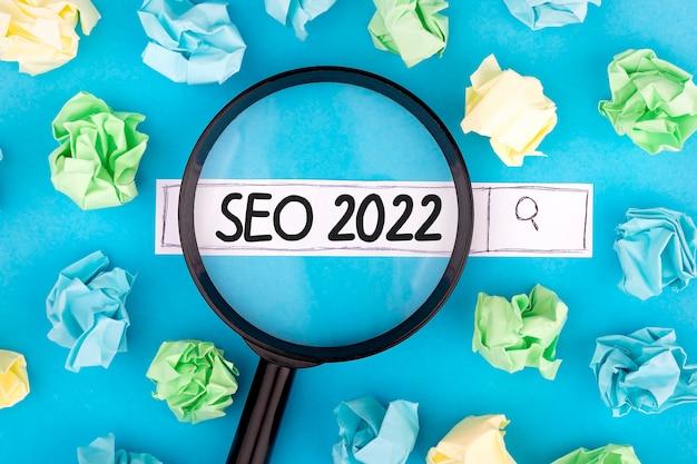 Concept de recherche. texte seo 2022 avec loupe et morceaux de papier sur fond bleu.