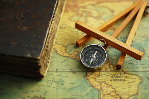 Concept de recherche de voyage et d'aventure. carte vieillie vintage avec un livre minable et une boussole. livre minable et boussole sur la table.