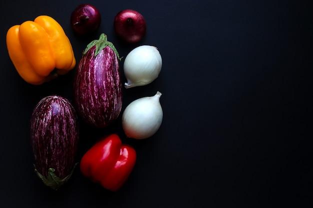 Concept de récolte légumes crus aubergines poivrons et oignons sur fond sombre