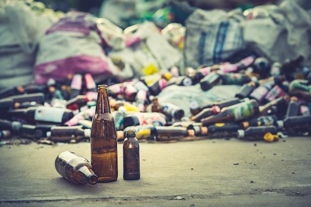 Concept de recyclage du verre, bouteille en verre à recycler sur le tas de bouteilles en verre floue.