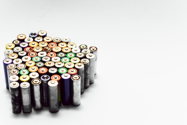 Concept de recyclage écologique, énergie de la nature, de nombreux types différents, batterie usagée, accumulateur rechargeable, piles alcalines sur fond blanc