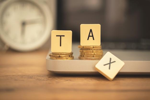 Le concept de réduction de la charge fiscale. bureau d'affaires avec ordinateur portable et réveil. photo d'arrière-plan du jour de l'impôt