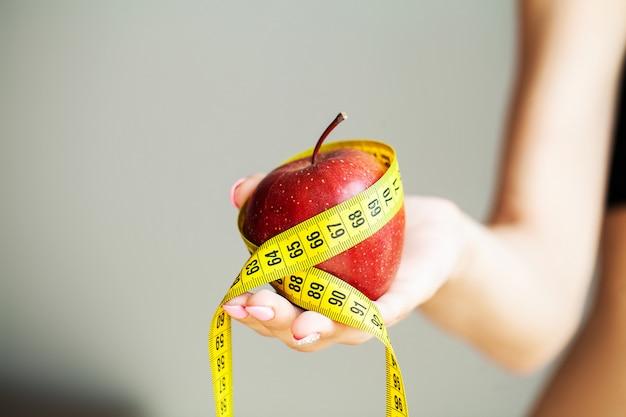 Concept de régime. apple avec du ruban de mesure dans la main féminine