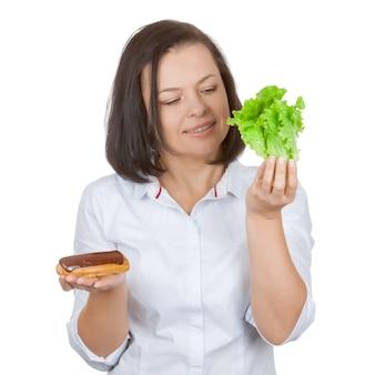 Concept de régime. belle jolie jeune femme choisissant entre éclair au chocolat et laitue sur fond blanc