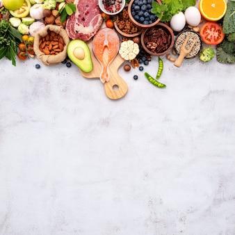 Concept de régime cétogène à faible teneur en glucides. ingrédients pour la sélection d'aliments sains mis en place sur fond de béton blanc.