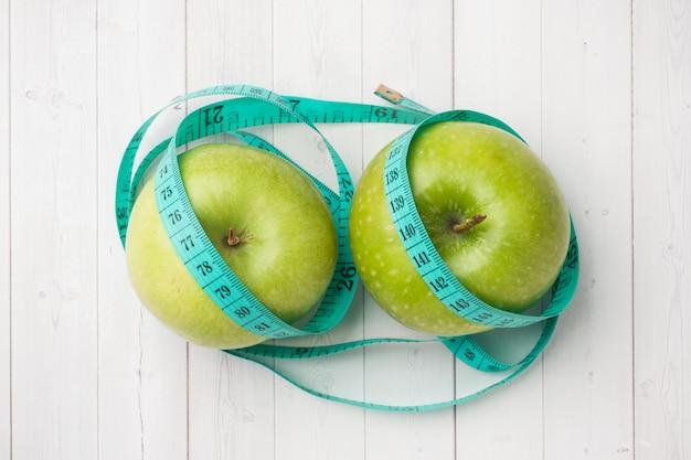 Concept de régime. deux pommes vertes et une roue de roulette sur une table blanche.