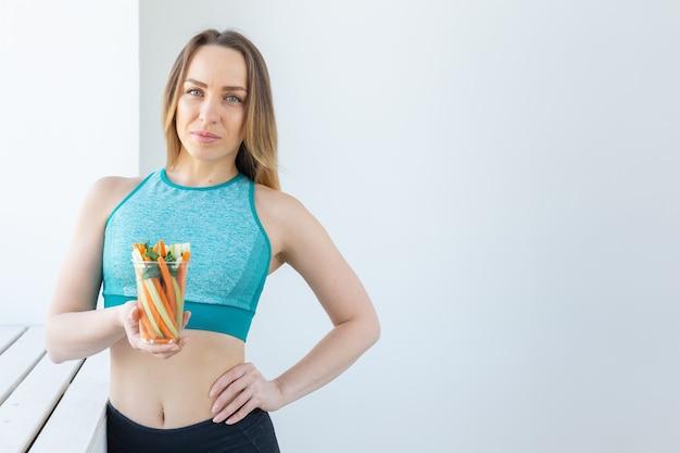 Concept de régime - femme de mode de vie sain tenant des légumes à l'intérieur. jeune femme mangeant des aliments sains