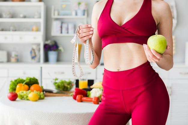 Concept de régime avec femme sportive en cuisine