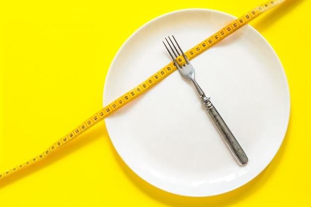 Concept de régime. fourchette sur une assiette blanche avec centimètre.