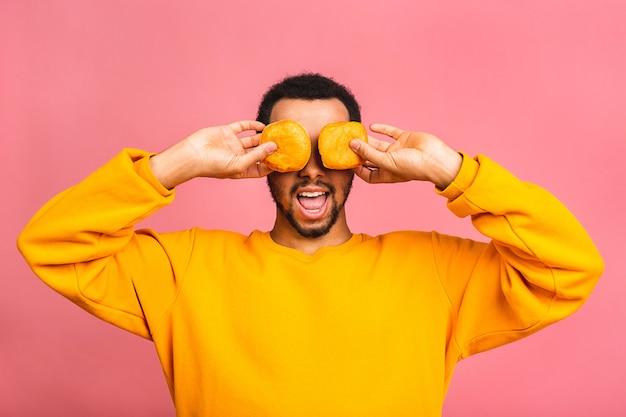 Concept de régime. homme barbu affamé, manger des beignets isolés sur rose.