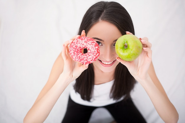 Concept de régime. jeune femme choisissant entre fruits et bonbons