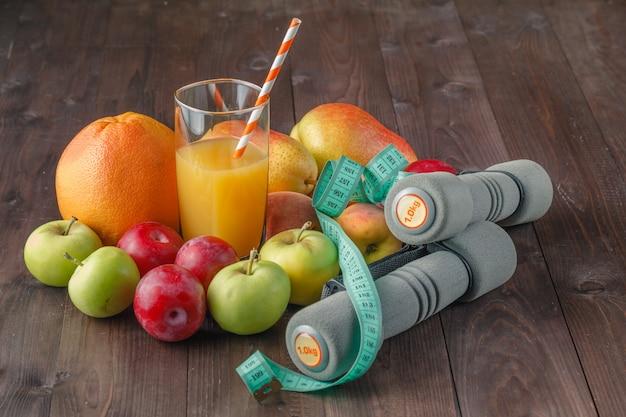 Concept de régime. jus frais en verre et haltères