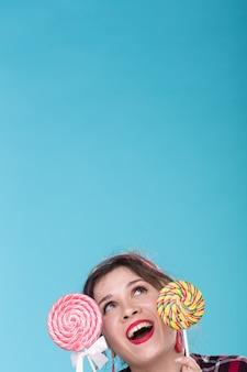 Concept de régime et de malbouffe - pin-up woman looking up sur une surface bleue avec copie espace