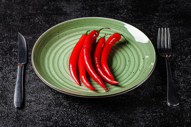 Concept de régime. le piment rouge se trouve sur une plaque verte