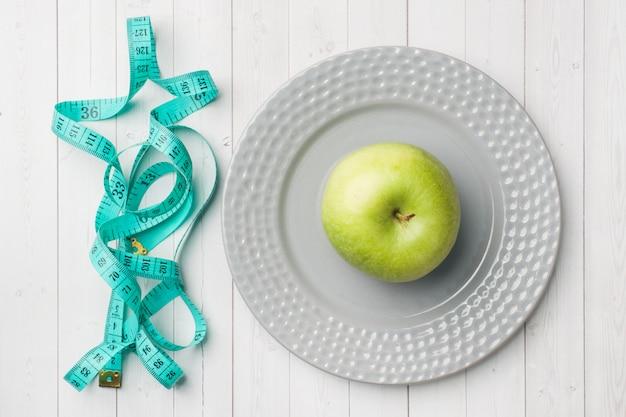 Concept de régime. pomme verte sur une assiette et ruban adhésif centimètre sur une table blanche.