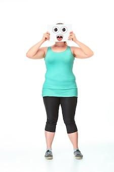 Concept de régime. portrait d'une grosse fille en pleine croissance avec sa bouche fermée par une feuille de papier avec un dessin sur fond de studio blanc