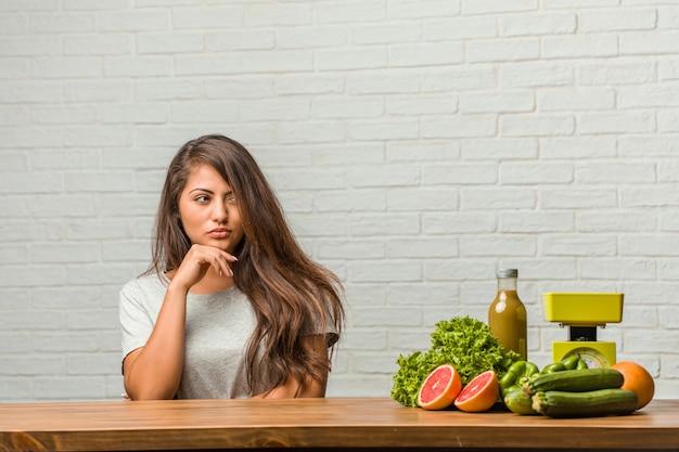 Concept de régime. portrait d'une jeune femme latine en bonne santé pensant et levant