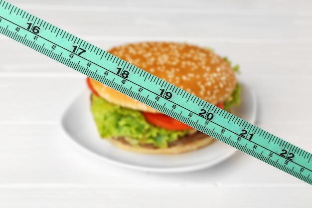 Concept de régime. ruban à mesurer et hamburger sur plaque