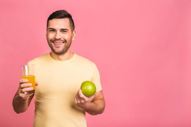 Concept de régime si savoureux et sain. séduisante jeune homme tenant un verre avec une boisson de désintoxication orange, fruits et légumes