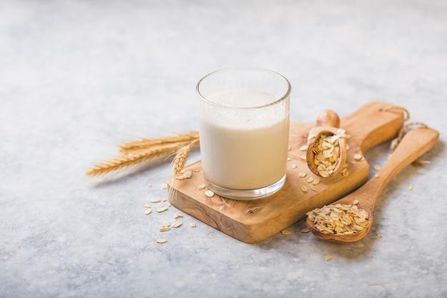Le concept d'un régime végétarien. lait d'avoine dans le verre avec pot de lait et d'avoine.