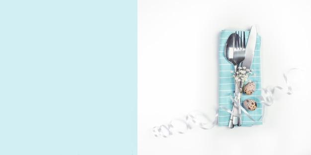 Concept de réglage de table de pâques. couverts décorés de fleurs blanches et de ruban et oeufs de caille sur serviette sur fond blanc et bleu clair avec espace copie.