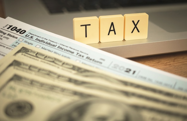 Concept de règlement fiscal. arrière-plan de temps d'imposition des états-unis avec des blocs de bois, un formulaire de demande de 1050 et des billets d'un dollar sur le bureau de l'entreprise