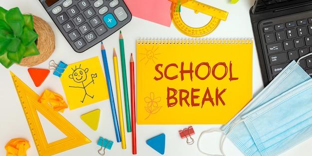 Concept de relâche scolaire. cahier ouvert avec fournitures scolaires