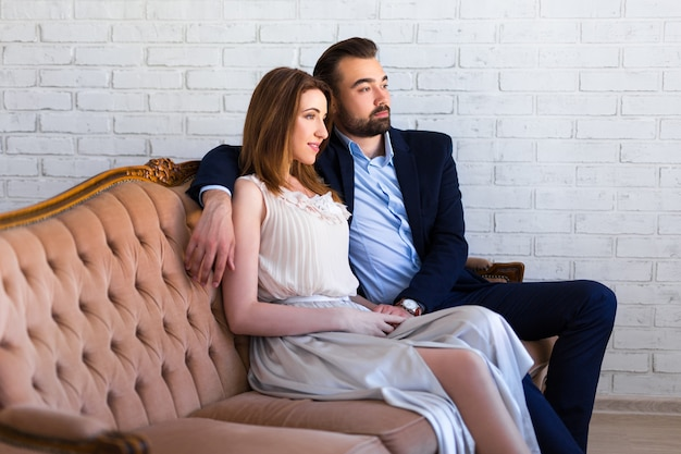 Concept de relation et d'amour - jeune beau couple assis et rêvant de quelque chose