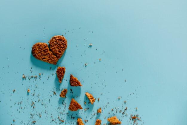 Concept de relation malheureuse. pose à plat de pain grillé tranché et brûlé en forme de cœur brisé. arrière-plan de la vue de dessus