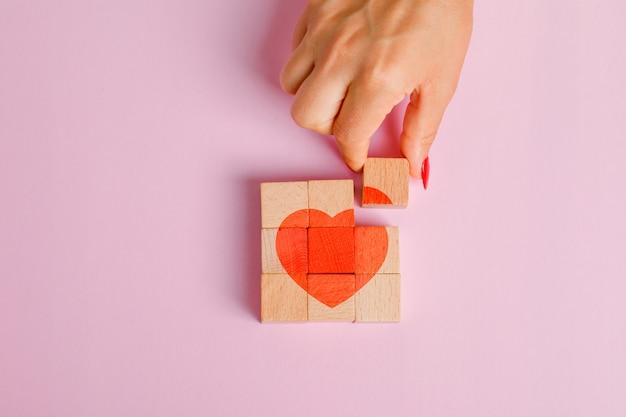 Concept de relation à plat. doigt tirant sur un bloc de bois.