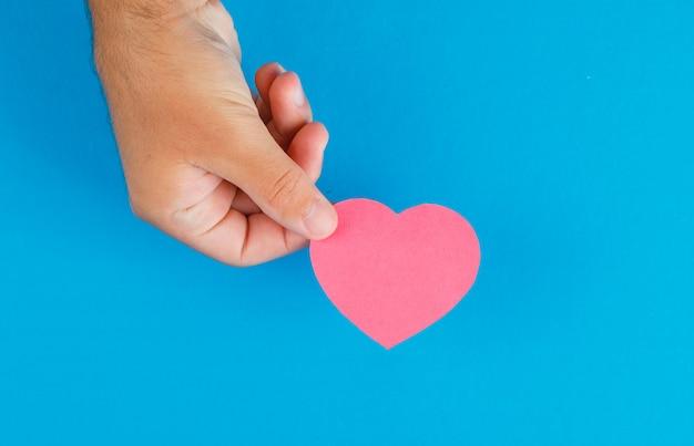 Concept de relation sur table bleue à plat. main tenant le coeur en papier découpé.