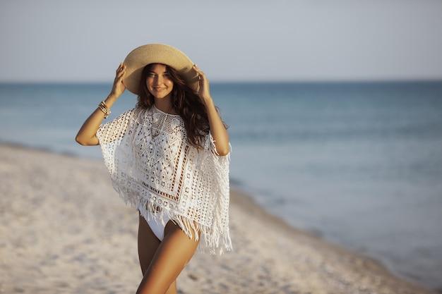 Concept de relaxation de vacances de voyage d'été. une jolie femme brune debout sur une plage de sable