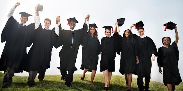 Concept de remise des diplômes levé groupe étudiants