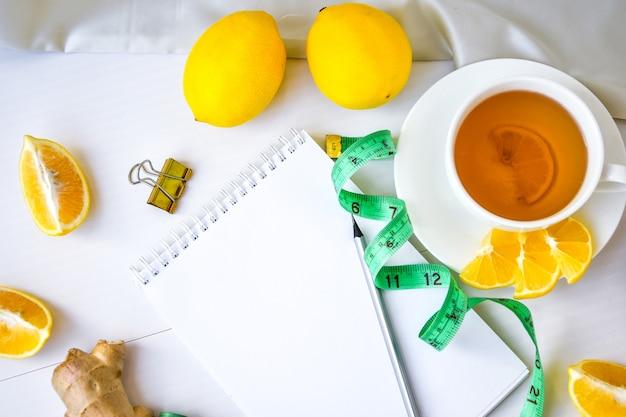 Concept de remise en forme au citron, gingembre, thé à la camomille, ruban à mesurer sur fond blanc. cahier vide avec espace de copie et crayon. concept de vie saine. recette.