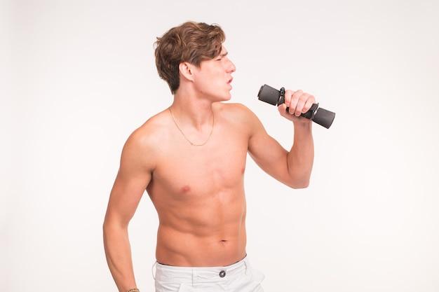 Concept de remise en forme, blague et personnes - portrait de bel homme athlétique chantant avec haltère sur blanc