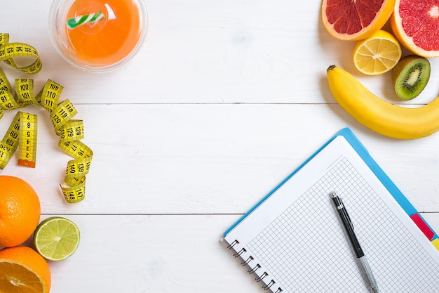 Concept de remise en forme avec des fruits un verre de jus et centimètre vue de dessus concept d'arrière-plan