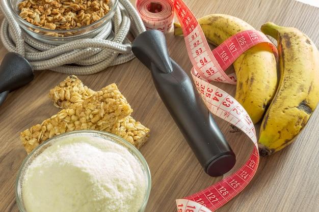 Concept de remise en forme avec des haltères, corde à mesurer protéines de lactosérum et bananes à sauter à la corde.