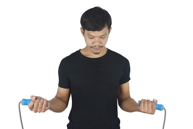Concept de remise en forme jeune homme fort et en bonne santé tenant une corde à sauter sur fond gris