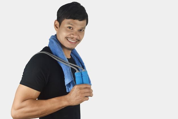 Concept de remise en forme jeune homme tenant une corde à sauter à ses épaules sur fond gris