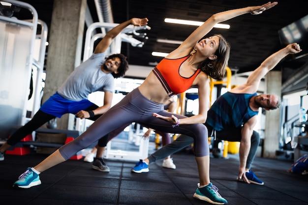 Concept de remise en forme, sport, entraînement et style de vie. groupe de personnes en forme faisant de l'exercice dans une salle de sport