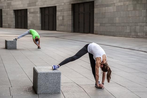 Concept de remise en forme, de sport, d'exercice, d'entraînement et de personnes - couple faisant des exercices de trempette des triceps sur le banc de la rue de la ville.