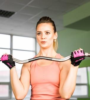 Concept de remise en forme, sport, formation et style de vie - femme heureuse avec haltères flexion des muscles dans la salle de gym