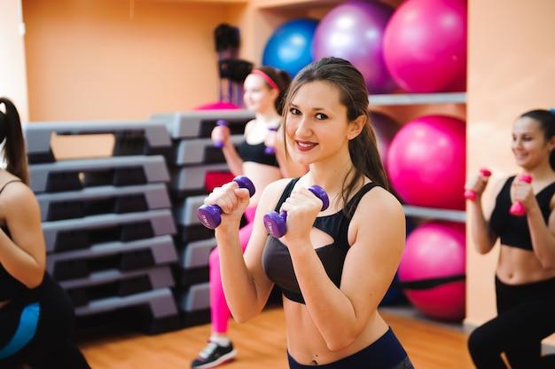 Concept de remise en forme, sport, formation et style de vie - groupe de femmes heureuses avec des haltères flexion des muscles dans la salle de gym