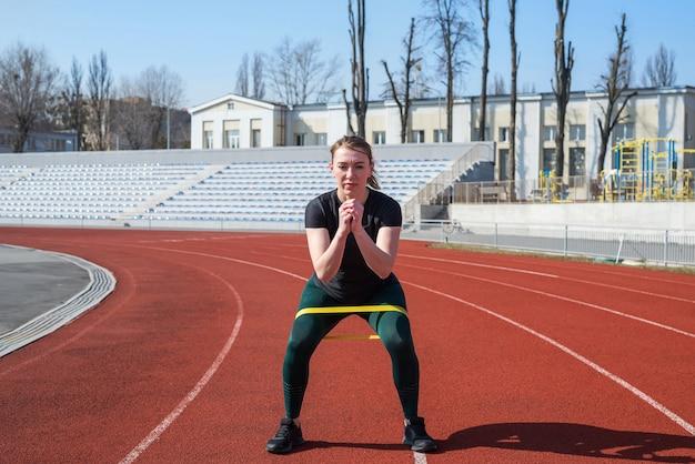 Concept de remise en forme et de sport. jeune femme sportive forme les jambes à l'aide d'élastiques de remise en forme sur la piste rouge.