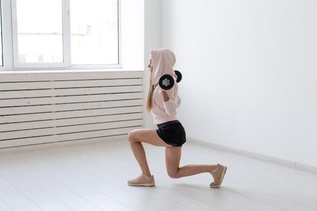 Concept de remise en forme, de sport et de personnes - femme sportive souriante avec haltères faisant des squats ou des fentes.