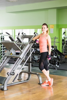 Concept de remise en forme, de sport et de personnes - portrait de jeune femme de remise en forme dans la salle de gym